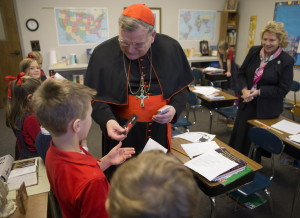 """Cardinal Raymond Leo Burke, the former bishop of La Crosse who now serves as chief justice of the Vatican supreme court, visits the second grade classroom of teacher Kris Baudek (right) Thursday, December 4, 2014 at Trinity Academy in Pewaukee, Wis. The 150 student student school espouses a traditional Roman Catholic education. Thursday evening he will speak on education as a means of cultural transformation at the Country Springs Hotel in Waukesha. As part of the event, Burke will sign copies of a new book he co-authored, titled, """"Remaining in the Truth of Christ."""" A Wisconsin native, Burke served as bishop of St. Louis before going to the Vatican in 2008. He was made a cardinal two years later. Burke confirmed in October that Pope Francis plans to remove him as prefect of the Vatican's Supreme Tribunal of the Apostolic Signatura, and install him in the largely ceremonial role as patron to the Sovereign Military Order of Malta.  MARK HOFFMAN/MHOFFFMAN@JOURNALSENTINEL.COM"""