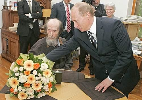 Russia's President Vladimir Putin (R) presents flowers to Alexander Solzhenitsyn after handing the State Prize for his achievements in humanitarian field as president visits his home in Troitse-Lykovo in Moscow, June 12, 2007. REUTERS/RIA Novosti/Kremlin (RUSSIA)