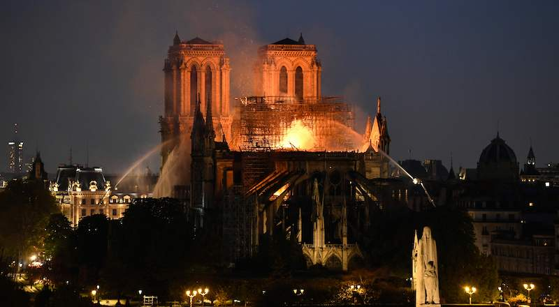 Firefighters douse flames rising from the roof at Notre-Dame Cathedral in Paris on April 15, 2019. - A major fire broke out at the landmark Notre-Dame Cathedral in central Paris sending flames and huge clouds of grey smoke billowing into the sky, the fire service said. The flames and smoke plumed from the spire and roof of the gothic cathedral, visited by millions of people a year, where renovations are currently underway. (Photo by Bertrand GUAY / AFP)